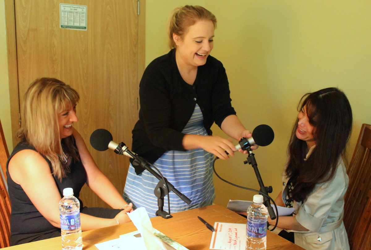 StoryCorps facilitator Jill sets up microphones for Gina (left) and Argelia. When Gina experienced homelessness, Argelia was her case manager. Now Gina is a service provider with the YWCA, and Argelia is her supervisor.