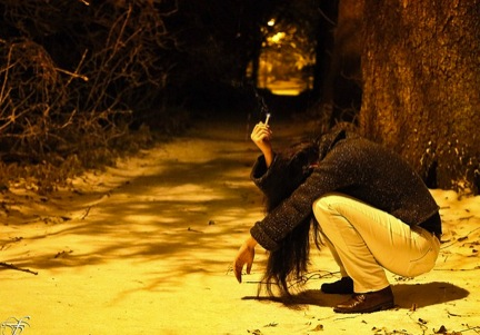Image of woman crouching outside