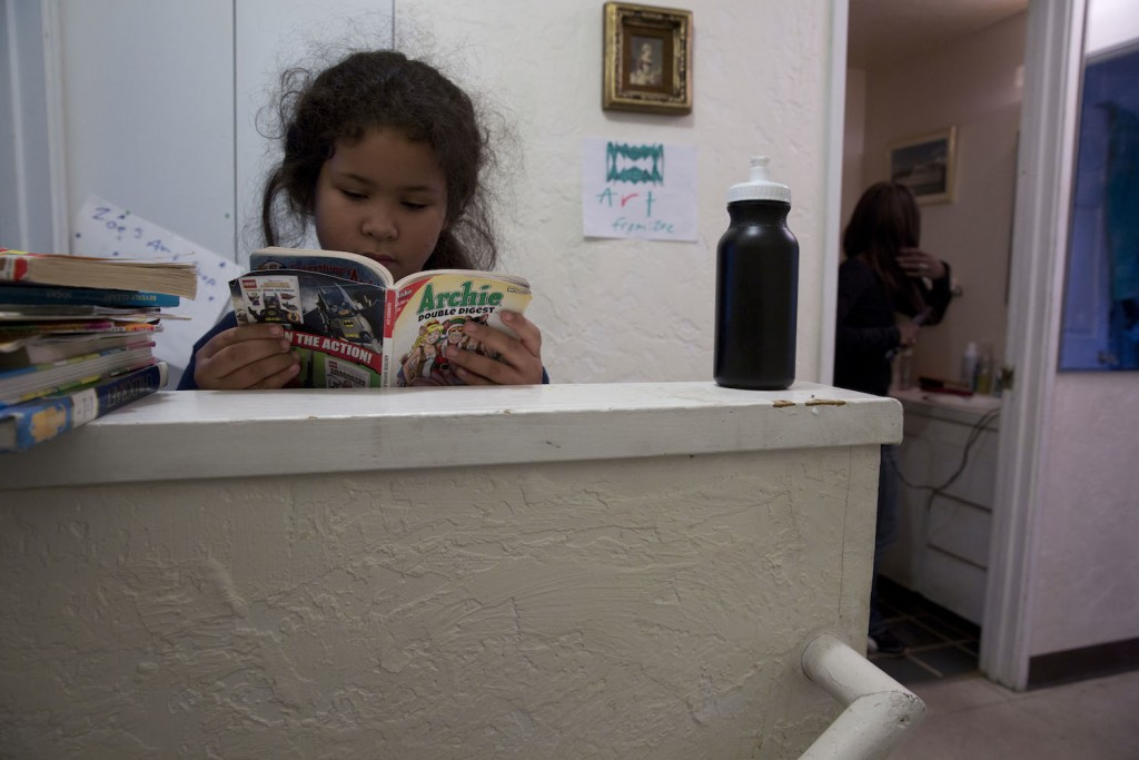 An avid reader, Zoe spends a few moments with a comic book while her mom prepares to walk her to school.