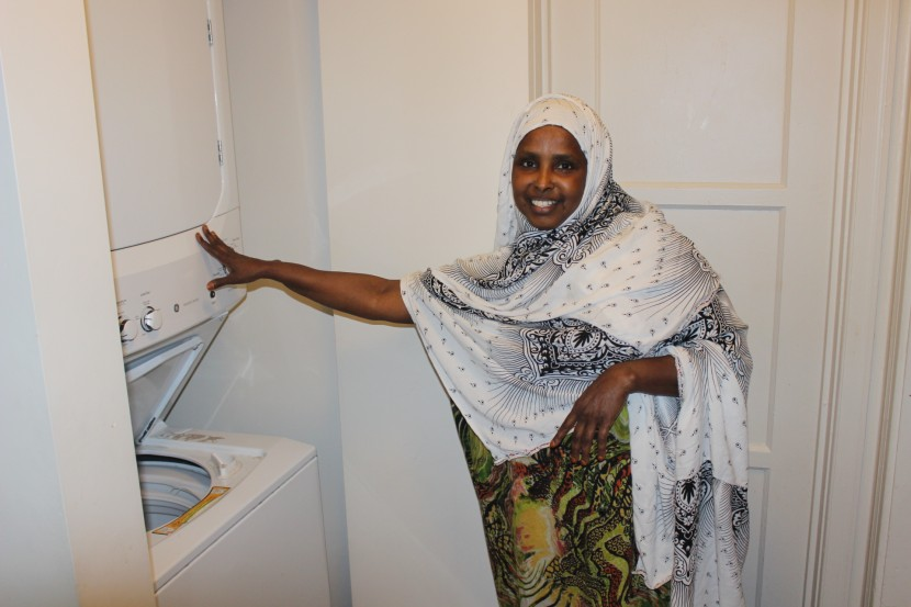 Sahro Farah shows off the washer and dryer at her new affordable apartment. This safe new home is a huge contrast from her previous apartment, where she lived with broken appliances and exposed wires.
